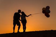 Schattenbild eines Paares, das mit Ballonen bei Sonnenuntergang spielt Stockfotos