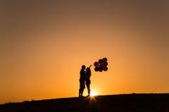 Schattenbild eines Paares, das mit Ballonen bei Sonnenuntergang spielt Lizenzfreies Stockfoto