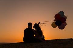 Schattenbild eines Paares, das mit Ballonen bei Sonnenuntergang spielt Lizenzfreie Stockfotografie
