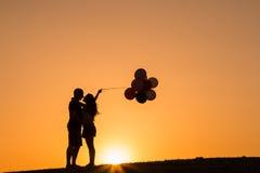 Schattenbild eines Paares, das mit Ballonen bei Sonnenuntergang spielt Lizenzfreie Stockbilder