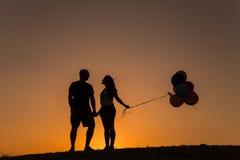 Schattenbild eines Paares, das mit Ballonen bei Sonnenuntergang spielt Lizenzfreies Stockbild