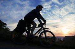 Schattenbild eines Radfahrers auf dem Hintergrund des bewölkten Himmels Stockbild