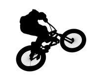Schattenbild eines Radfahrers, der auf ein Fahrrad springt Lizenzfreie Stockfotos