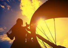 Schattenbild eines Radfahrers, der ein Fahrrad auf den Hintergrund des bewölkten Himmels reitet Stockbilder