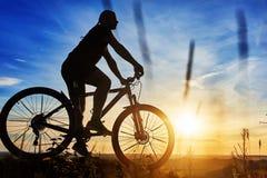 Schattenbild eines Radfahrers mit einem Fahrrad auf Himmelhintergrund auf schönem Sonnenuntergang Lizenzfreies Stockfoto