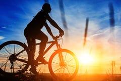 Schattenbild eines Radfahrers mit einem Fahrrad auf Himmelhintergrund auf schönem Sonnenuntergang Lizenzfreie Stockbilder