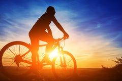 Schattenbild eines Radfahrers mit einem Fahrrad auf Himmelhintergrund auf schönem Sonnenuntergang Stockfotos