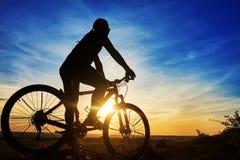 Schattenbild eines Radfahrers mit einem Fahrrad auf Himmelhintergrund auf schönem Sonnenuntergang Stockfotografie