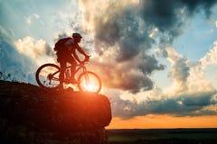 Schattenbild eines Radfahrers und des Fahrrades auf Himmelhintergrund Lizenzfreie Stockfotografie