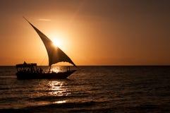 Schattenbild eines Segelboots bei Sonnenuntergang in einem ruhigen Ozean stockbild