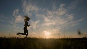 Schattenbild eines sexy Sitzfrauenmädchens, das bei Sonnenuntergang läuft Ausbildung, rüttelnd, gesunder Lebensstil