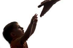 Schattenbild eines Sohns, der seine Arme zu seinen Vater ` s Händen ausdehnt Lizenzfreie Stockbilder