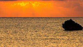 Schattenbild eines Steins auf einem Hintergrund eines Sonnenuntergangs Lizenzfreies Stockbild