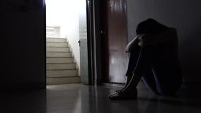 Schattenbild eines traurigen jungen Mädchens, das in der Dunkelheit sich lehnt an der Wand in der alten Eigentumswohnung, häuslic stock video