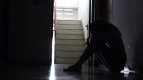 Schattenbild eines traurigen jungen Mädchens, das in der Dunkelheit sich lehnt an der Wand in der alten Eigentumswohnung sitzt stock footage