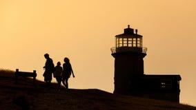Schattenbild einiger Leute und des Leuchtturmes in England Lizenzfreie Stockbilder