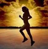 Schattenbild-Frau, die auf Strand läuft Stockfotografie