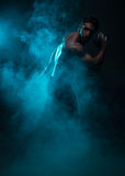 Schattenbild-hemdloser Mann mit Muskeln, der im Rauche aufwirft Lizenzfreies Stockbild