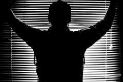 Schattenbild im Monochrom des Mannes auf dem Fenster, das mit gestreiftem Licht und Schatten Fensterläden schließt Stockfotografie