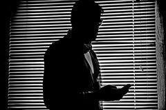 Schattenbild im Monochrom des Mannes mit seinem Handy iPhone in der Dunkelheit Lizenzfreie Stockbilder