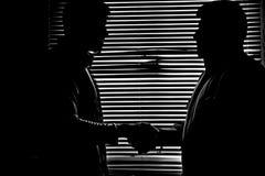 Schattenbild im Monochrom von zwei Männern, die Handdunkelheit rütteln lizenzfreies stockfoto