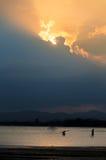 Schattenbild im Sonnenuntergang für Folkways kleine Gruppe auf Küste Lizenzfreies Stockfoto