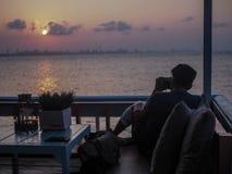 Schattenbild Junge die wie zu reisen und Fotograf, Fotos der schönen Momente während des Sonnenuntergangs machend, Sonnenaufgang Lizenzfreies Stockbild