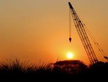 Schattenbild-Kran auf Sonnenuntergang-Hintergrund in Thailand Stockbilder