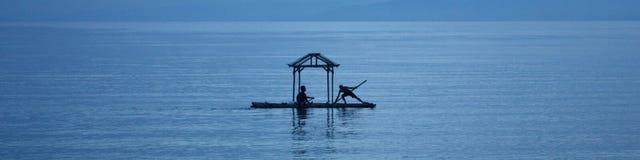 Schattenbild-Männer auf Floss im China-Meer Stockfoto