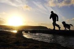 Schattenbild-Mann, der mit Hund läuft. Stockfotos