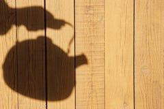 Schattenbild mit Kessel auf der natürlichen Holzverkleidung Lizenzfreies Stockbild