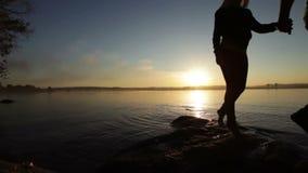 Schattenbild-Paare, die untergehende Sonne verlassen stock video footage