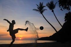 Schattenbild-Salven-Trittfußball auf dem Strand, asiatischer Mannspielfußball bei Sonnenaufgang stockfotografie