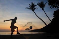 Schattenbild-Salven-Trittfußball auf dem Strand, asiatischer Mannspielfußball bei Sonnenaufgang stockbild
