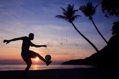 Schattenbild-Salven-Trittfußball auf dem Strand, asiatischer Mannspielfußball bei Sonnenaufgang lizenzfreie stockfotografie