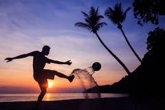 Schattenbild-Salven-Trittfußball auf dem Strand, asiatischer Mannspielfußball bei Sonnenaufgang lizenzfreies stockfoto