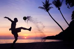 Schattenbild-Salven-Trittfußball auf dem Strand, asiatischer Mannspielfußball bei Sonnenaufgang lizenzfreies stockbild