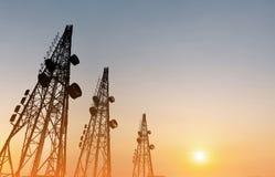 Schattenbild, Telekommunikation ragt mit Fernsehantennen und -Satellitenschüssel im Sonnenuntergang hoch stockfotos