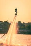 Schattenbild und Weinlese färben styl des Zeigens von flyboard auf Chaophya Lizenzfreies Stockfoto