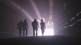 Schattenbild vieler Bauarbeiter, die heraus von einem großen Tunnel gehen stock footage