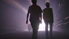 Schattenbild vieler Bauarbeiter, die heraus von einem großen Tunnel gehen