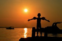 Schattenbild von ausgebreiteten Händen des kleinen Jungen mit Schwimmenärmeln auf Armen in Richtung zum Sonnenuntergang auf molo  Stockbild