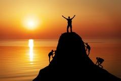Schattenbild von a bemannt auf eine Gebirgsoberseite auf Sonnenunterganghintergrund stockfoto
