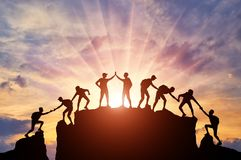 Schattenbild von Bergsteigern, die zur Spitze der Gebirgsdank Rechtshilfe und Teamwork kletterten stockfoto
