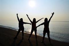 Schattenbild von 3 Damen mit Sonnenaufgang auf dem Strand stockfoto
