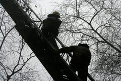 Schattenbild von den Feuerwehrmännern, die ein rasendes Feuer mit enormen Flammen kämpfen Lizenzfreie Stockbilder