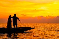 Schattenbild von den Fischern, die im See zur Sonnenaufgangzeit fischen Lizenzfreie Stockfotos