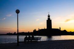 Schattenbild von den Frauen, die auf Bank, StockholmRathaus, Schwede sitzen lizenzfreies stockbild