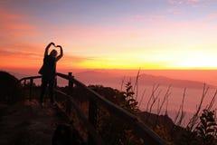 Schattenbild von den Frauen, die Herzzeichen mit Sonnenaufgang und Nebelhintergrund machen Lizenzfreies Stockbild
