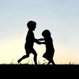Schattenbild von den glücklichen kleinen Kindern, die bei Sonnenuntergang tanzen lizenzfreies stockbild